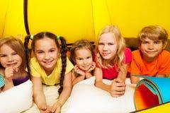 Fem lyckliga ungar som lägger i tält och leende Royaltyfri Foto