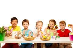 Fem lyckliga ungar som tillsammans målar östliga ägg Arkivbild