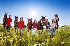 Fem lyckliga ungdomarmed deras hästar i fält Arkivbilder