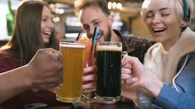 Fem lyckliga vänner som klirrar exponeringsglas med öl och coctailar i stången, bar arkivfilmer