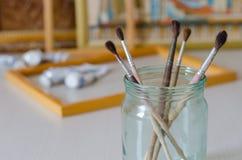 Fem målarpenslar i en exponeringsglaskrus Bildramar, målarfärg arkivfoto