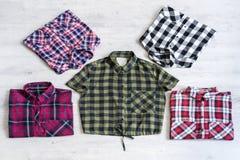 Fem mång--färgade rutiga skjortor för kvinna` som s ligger trevligt vikt Royaltyfria Foton