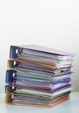 Fem mappar med dokument som staplas i en hög på tabellen Arkivfoton
