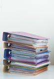 Fem mappar med dokument som staplas i en hög på tabellen Arkivbilder
