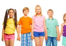 Fem nätta ungar i rad på vit Arkivfoto