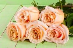 Fem nya beigea rosor på en grön träbakgrund Arkivbilder