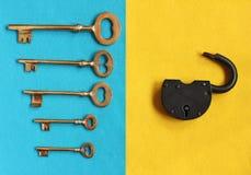 Fem olika guld- tangenter på blå filt och den öppna hänglåset på skrän Arkivfoton