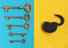 Fem olika guld- tappningtangenter på blå filt och den öppna hänglåset Arkivfoto
