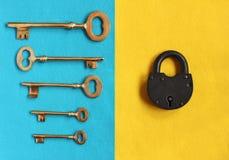 Fem olika guld- tappningtangenter på blå filt och stänger padloc Royaltyfri Foto