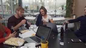 Fem olika kollegor i jubellynnet som klirrar exponeringsglas med pepsi, medan fira något i modernt kontor stock video