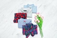 Fem olika skjortor och en bukett av tulpan Trendig conce Royaltyfri Bild