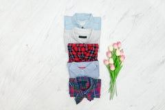 Fem olika skjortor och en bukett av tulpan Trendig conce Fotografering för Bildbyråer