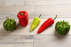 Fem olika sorter av peppar på ett träbräde Royaltyfri Foto