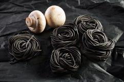 Fem portioner av svart pasta med bläckfiskfärgpulver och mushroo två Royaltyfri Fotografi