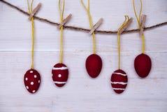 Fem röda påskägg som hänger på linje Royaltyfri Foto