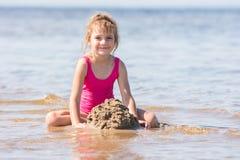 Fem-året flickan i en rosa baddräkt som spelar i sand i, blir grund av floden Royaltyfria Foton