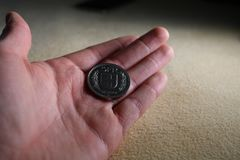 Fem schweizisk franc mynt i en hand Arkivbild