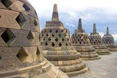 Fem stupas som conceling Budda statyer, Borobudur, Indonesien Arkivbild