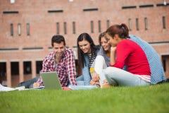 Fem tillfälliga studenter som sitter på gräset som ser bärbara datorn Royaltyfri Foto