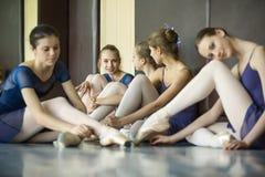 Fem unga dansare i de samma dansdräkterna som vilar sammanträdenolla Arkivfoton