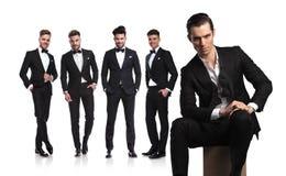 Fem unga män i tuxedoes med ledaren som framme sitter royaltyfri bild