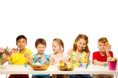 Fem ungar med färgglade östliga ägg på tabellen Royaltyfri Bild