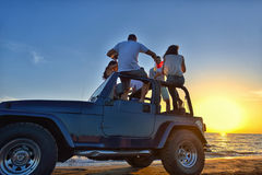 Fem ungdomarsom har gyckel i konvertibel bil på stranden på solnedgången arkivfoton
