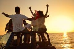 Fem ungdomarsom har gyckel i konvertibel bil på stranden på solnedgången Royaltyfri Bild