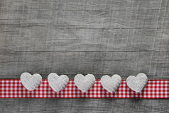 Fem vita hjärtor på en gammal grå träbakgrund med en checke Arkivfoto