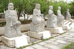 Fem vita marmorBuddhastatyer i en trädgård, Kina Arkivbild