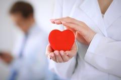 Femail arts die een rood hart in zijn handen op een achtergrond van de patiënt houden royalty-vrije stock fotografie