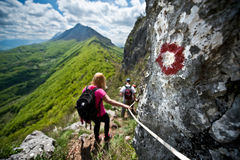 Femail hiker on a steep trail holding on to ropes. Femail hiker on a steep trail on a beautiful sunny day holding on to ropes Stock Photo