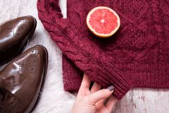 Femaile hand holding maroon knitted sweater, brown patent leather shoes, cut grapefruit halves. Wooden background, close up. Fashi Royalty Free Stock Photography