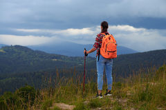 Femake hiker standing with backpack and poles on the mountain Royalty Free Stock Photo