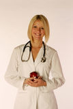 Female. Doctor holding an apple Stock Images