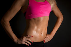 Female abs. Female abdominal muscles on a black background royalty free stock image
