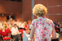 Female academic professor lecturing. Female academic professor lecturing at Conference. Audience at the lecture hall stock images