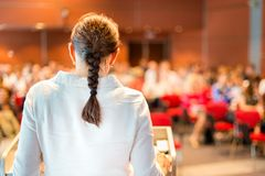 Female academic professor lecturing at faculty. Female academic professor lecturing at Conference. Audience at the lecture hall Royalty Free Stock Photo