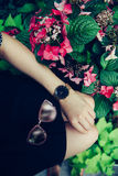 Female accessories concept. Sunglasses, golden watch and black skirt. Stock Images