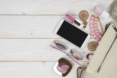 Female accessories falling from handbag on wooden background with copyspace Royalty Free Stock Image