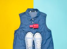 Female accessories, shoes and clothing layout on a blue yellow pastel background. Jeans shirt, sneakers, perfume bottle. Top view.  Royalty Free Stock Images