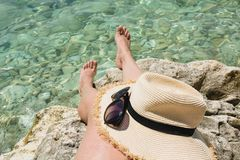 Female accessory, straw sunhat, glasses and long legs. Clean sea. Summer vacation. Close up. Female accessory, straw sunhat,sun glasses and long legs. Clean sea royalty free stock images