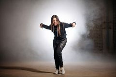 Female accompaning her speach with gestures.rapping on the smoky stage. Expressing gesture Royalty Free Stock Image