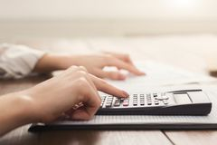 Female accountant or banker making calculations. Close up of female accountant or banker making calculations. Savings, finances and economy concept, copy space stock photo
