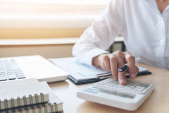 Female accountant calculations and analyzing financial graph dat. A with calculator and laptop Business, Financing, Accounting, Doing finance, Economy, Savings stock image
