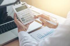 Female accountant calculations and analyzing financial graph dat. A with calculator and laptop Business, Financing, Accounting, Doing finance, Economy, Savings stock photos