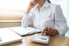 Female accountant calculations and analyzing financial graph dat. A with calculator and laptop Business, Financing, Accounting, Doing finance, Economy, Savings royalty free stock images