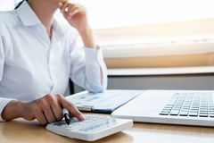 Female accountant calculations and analyzing financial graph dat. A with calculator and laptop Business, Financing, Accounting, Doing finance, Economy, Savings Stock Photo