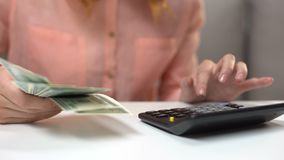 Female accountant counting dollar banknotes, housewife planning family budget stock footage