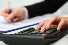 Female accountant hand holding pen counting on calculator Royalty Free Stock Photo